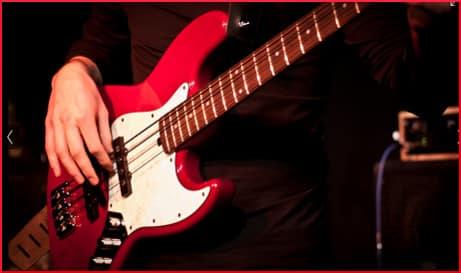 Man plucking bass guitar
