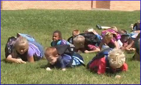 schoolchildren lying on grass