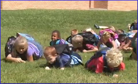 schoolchildren lying on grass