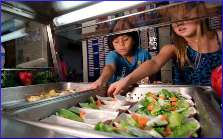 [children reaching for salads at school cafeteria]
