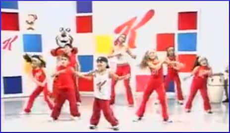 [children dancing in front of Kellogg logo]