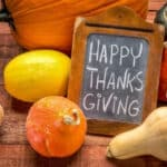 46177351 - happy thanksgiving  - white chalk handwriting on a small blackboard surrounded by pumpkin and winter squash