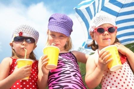 three-girls-on-beach-drinking-juice